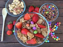 Cuencos con las escamas, las fresas, los cacahuetes y el caramelo coloreado Imágenes de archivo libres de regalías
