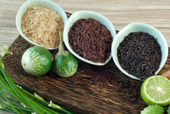 3 cuencos de arroz crudo; arroz marrón, rojo, y negro Imagen de archivo