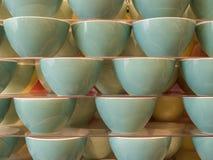 Cuencos de cerámica de formyvystavleny clásico en varias filas en mercancías de la demostración-ventana de la tienda imagenes de archivo