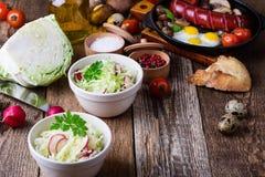 Cuencos de ensalada de las verduras frescas con la col y el rábano Imagenes de archivo
