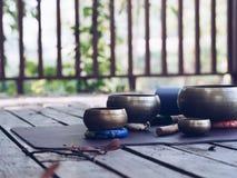 Cuencos de la estera y del canto de la yoga para el maditation en la madera en naturaleza fotografía de archivo libre de regalías