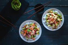 Cuencos del sushi del rollo de California en el fondo oscuro, visión superior foto de archivo