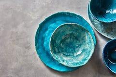 Cuencos y placas azules de la porcelana en una tabla gris Platos hechos a mano del vintage de cerámica colorido Endecha plana fotos de archivo