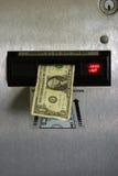 Cuenta de dólar en una máquina de cambio Imagen de archivo libre de regalías