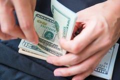 Cuenta de dólares americanos del dinero con la mano Foto de archivo
