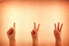 Cuenta de las manos a partir de la una a tres contra un sucio Imagen de archivo libre de regalías