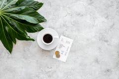 Cuenta del restaurante de la paga Bill, tarjeta de banco, acuña cerca de la taza de café en copyspace ligero de la opinión de sob Foto de archivo