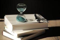Cuenta descendiente del reloj de arena con libros y una pluma Foto de archivo