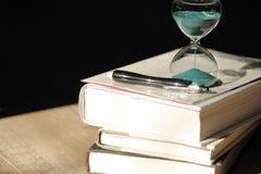 Cuenta descendiente del reloj de arena con libros y una pluma Fotos de archivo