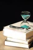 Cuenta descendiente del reloj de arena con libros y una pluma Imágenes de archivo libres de regalías