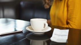 Cuenta que paga de la mujer y café el irse, prisa para el trabajo, tradición del café de la mañana almacen de video
