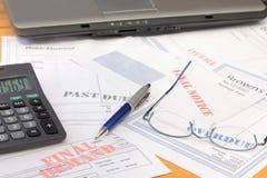 Cuentas atrasadas con la calculadora y la computadora portátil foto de archivo