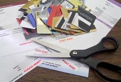 Cuentas atrasadas, tijeras, y tarjetas de crédito cortadas Fotografía de archivo