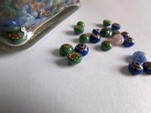 Cuentas de cristal multicoloras hechas a mano en la superficie blanca con la luz suave Fotos de archivo