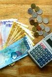 Cuentas de dinero en una tabla y una calculadora Fotos de archivo