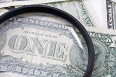 Cuentas de dólar de EE. UU. vistas a través de la lupa, cierre para arriba Imágenes de archivo libres de regalías