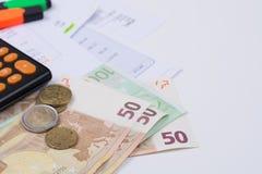 Cuentas de la utilidad o de la hipoteca, calculadora y billete de banco y moneda del euro Foto de archivo