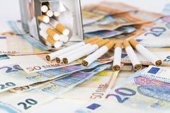 Cuentas euro de los billetes de banco con los cigarrillos Imágenes de archivo libres de regalías