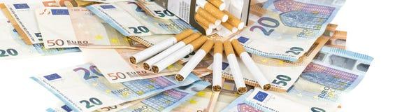 Cuentas euro de los billetes de banco con los cigarrillos Fotografía de archivo libre de regalías