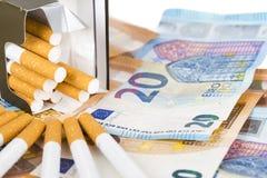 Cuentas euro de los billetes de banco con los cigarrillos Foto de archivo libre de regalías
