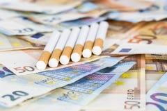 Cuentas euro de los billetes de banco con los cigarrillos Fotos de archivo libres de regalías
