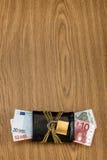 Cuentas euro en una cartera bloqueada con la cadena de oro y el candado Foto de archivo libre de regalías
