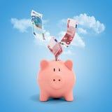 Cuentas euro que caen adentro o que vuelan fuera de una hucha rosada Fotografía de archivo