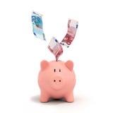 Cuentas euro que caen adentro o que vuelan fuera de una hucha rosada Fotos de archivo