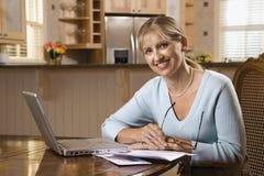 Cuentas que pagan de la mujer en el ordenador. Fotos de archivo