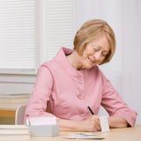 Cuentas que pagan sonrientes de la mujer con las verificaciones en el escritorio Foto de archivo libre de regalías