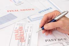 Cuentas y facturas atrasadas con la pluma a disposición fotos de archivo