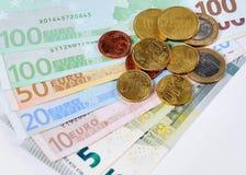 Cuentas y monedas euro con el fondo blanco Imagen de archivo libre de regalías
