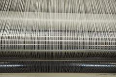 Cuente un cuento la máquina de combeo en una fábrica que teje de la materia textil Imágenes de archivo libres de regalías