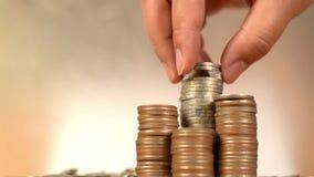 Cuente y ponga las monedas del dinero a la pila de monedas almacen de metraje de vídeo