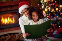 Cuentos de hadas de la Navidad de la lectura de la mamá y de la hija fotos de archivo libres de regalías