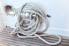 Cuerda blanca arrollada en una cubierta de barcos de madera fotografía de archivo libre de regalías