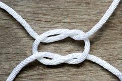 Cuerda blanca en forma del nudo de filón en el fondo de madera Fotos de archivo libres de regalías