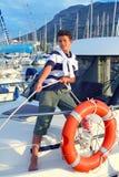 Cuerda de barco adolescente de la amarradura del marinero del muchacho en puerto Imagen de archivo libre de regalías