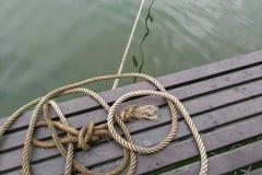 Cuerda de barco, nudo de la cuerda en la madera y agua Imagen de archivo libre de regalías