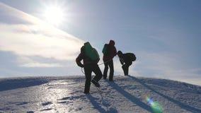 Cuerda de la subida de tres Alpenists en la montaña nevosa Los turistas trabajan juntos como alturas de sacudida del equipo que s metrajes