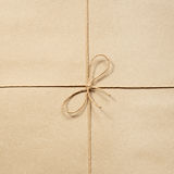 Cuerda de papel, anudada en el beige del papel de embalaje Foto de archivo libre de regalías