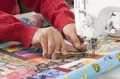 Cuerda de rosca del corte de Quilter en la máquina de coser. Fotografía de archivo