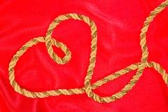 Cuerda de rosca del oro en el satén rojo Imagenes de archivo
