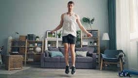 Cuerda de salto deportiva del estudiante del individuo en el apartamento que ejercita solamente disfrutando de deportes almacen de video