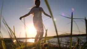 Cuerda de salto de la muchacha en puesta del sol de la tarde Cámara lenta almacen de metraje de vídeo