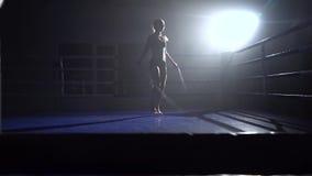 Cuerda de salto de la muchacha en un cuarto oscuro Silueta Cámara lenta almacen de video