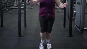 Cuerda de salto masculina gorda, calentando antes de entrenamiento del gimnasio, ejercicio cardiio almacen de video