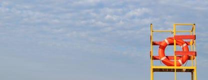 Cuerda de salvamento anaranjada en torre amarilla del salvavidas en fondo del cielo azul bandera fotografía de archivo