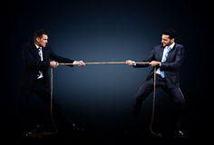Cuerda de tracción de dos hombres de negocios en una competencia Imágenes de archivo libres de regalías