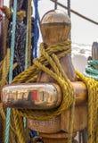 Cuerda del amarre atada en los bolardos de la nave de madera vieja Foto de archivo